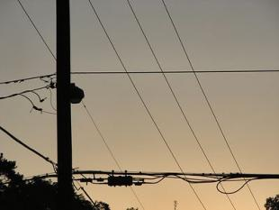electrical lines silhouetted against a sunset