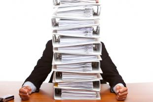 Person behind stack of binders