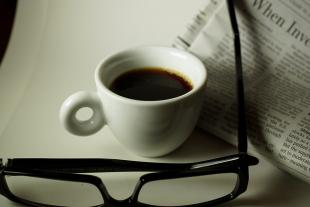 Glasses and a cup of coffee resting next to a newspaper on a white table