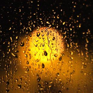 Light shining through a window speckled with rain