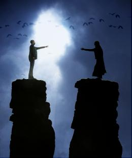 Two people standing on tall peaks reaching out to each other across the chasm