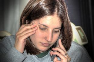 A woman talks on the phone, rubbing her temple and feeling stressed