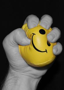 Man clutching stress ball angrily