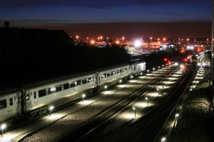 Train running through a train yard at high dusk