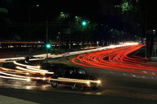 Car zipping around a corner with a light trail