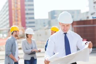 Business people wearing safety hats looking at blueprints