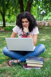 Young woman elearning on a laptop outside